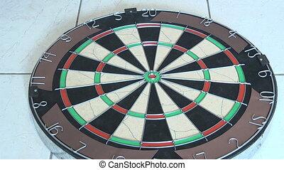 darts being thrown into dart board