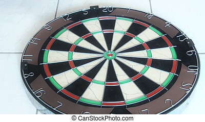 darts being thrown into dart board - the viewer is not lost...