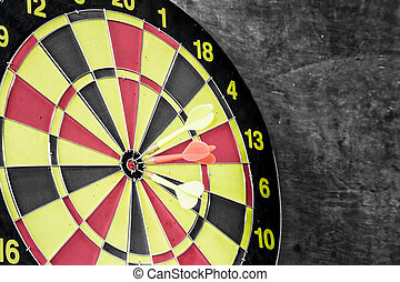 Darts board on cement background - dart hitting a same...