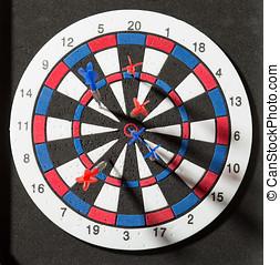 Darts hit dartboard - Red and blue darts hit dartboard
