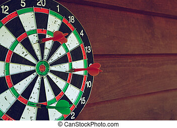 Darts over wooden background. Arrows missed target. Coyspace...
