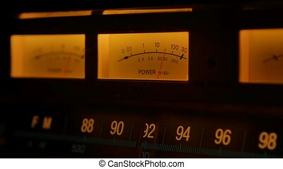Dashboard vintage radio receiver and amplifier with fm scale backlit yellow. Tuning analog radio frequency on scale of the retro receiver. Searching for stations on the radio. Close up. Slow motion
