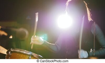 Dashing girl with black hair percussion drummer starts playing drums