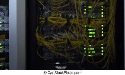 Datacenter. Flashing server rack rows of green lamps. Blurred background.