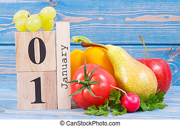 Date 1 January on calendar and fruits with vegetables, concept of healthy lifestyle and eating in new year