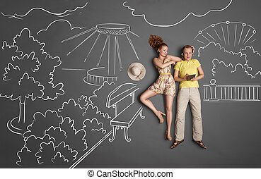 Love story concept of a romantic couple against chalk drawings background. Male wearing headphones and surfing internet, female trying to gain his attention.