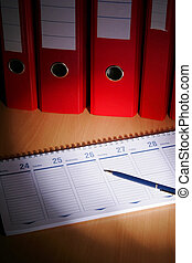 Date book on desck with red files on background
