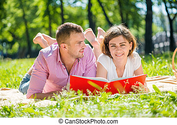 Date in park - Young romantic couple lying in park and...