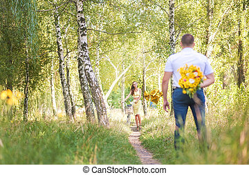 Date in the forest. A man with flowers behind his back is waiting for a woman on a bicycle
