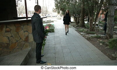 date of a young couple. man gives flowers to his girlfriend