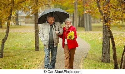 Date Under Rain - Senior couple having a rainy day date