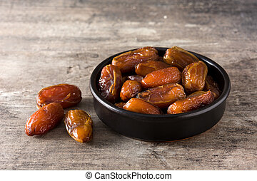Dates in black bowl on wooden table
