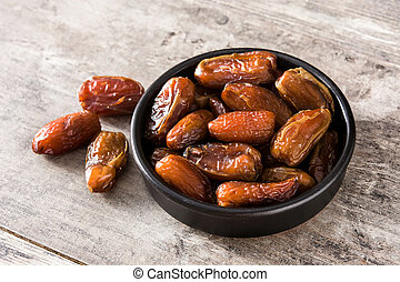 Dates in black bowl on wooden table.