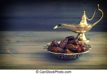 Dates in golden bowl and arabian Aladdin lamp. Vintage style