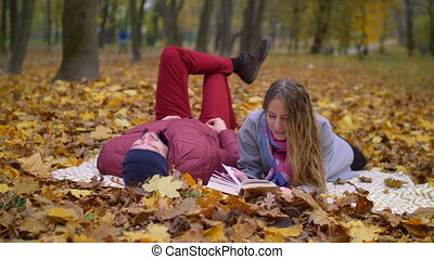 Dating couple reading a book in autumn nature - Attractive...