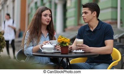 Dating couple relaxing together in street cafe