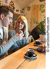 Dating - Couple in the cafe, he is holding a cupcake. Narrow...