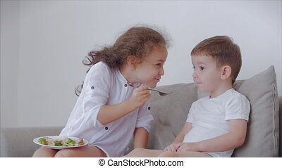 Daughter a pretty sister, nanny with a younger brother are sitting on the couch,loving happy sister takes care of her little brother, amuses the child,feeds him rice porridge with fish, teaches him how to eat, chew food.