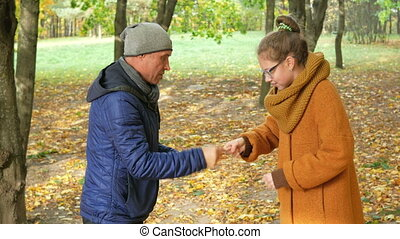 Daughter and father playing scissors paper stone in autumn park. Both laugh because his family had fun time