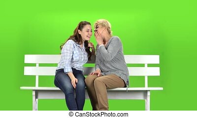 Daughter and mom are sitting on a bench. Green screen