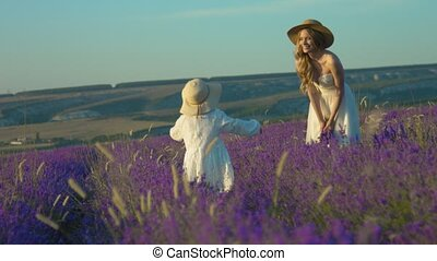 Daughter and mom send each other air kisses in the flowering field of lavender