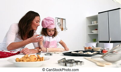 Daughter and mother baking cookies in the kitchen