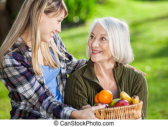 Daughter And Mother Holding Fruit Basket At Campsite