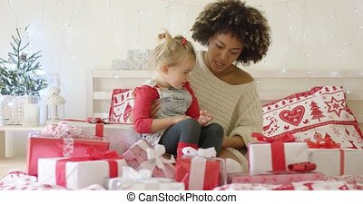 Daughter and mother in bed with Christmas gifts - Cute...