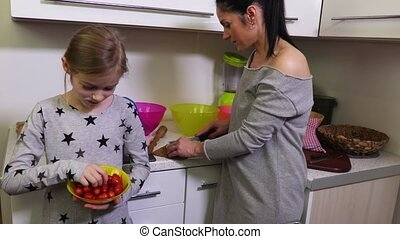 Daughter and mother make salads in kitchen