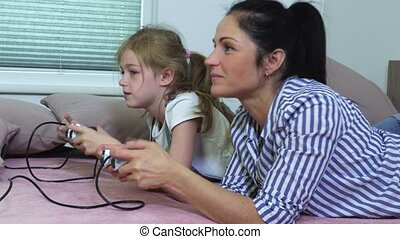 Daughter and mother playing computer game at home