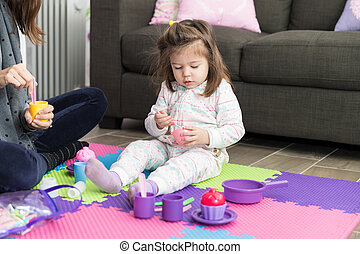 Daughter And Mother Playing Tea Party At Home