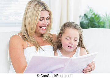 Daughter and mother reading book on the sofa