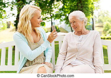daughter and senior mother with smartphone at park