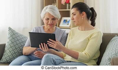 daughter and senior mother with tablet pc at home - family, ...