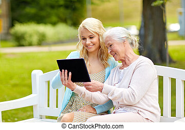 daughter and senior mother with tablet pc at park