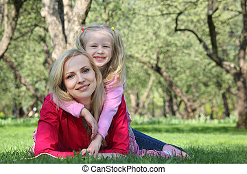 daughter embraces behind mother lying on grass in park