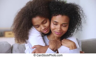 Daughter embracing mother closed eyes enjoy moment of...