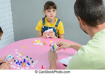 Daughter funny looks at dad, playing a board game at the table