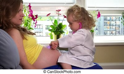 daughter girl and pregnant mother woman playing doctor with stethoscope