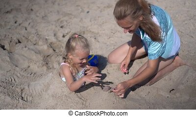 daughter girl buried in sand and her mom playing with sand. Blurred people and sea ocean on background. Camera motion shot with gimbal.