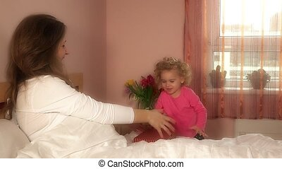 daughter girl give mother woman day birthday present in bed....