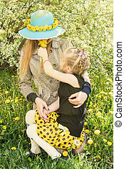 Daughter gives mom a sniff of dandelions