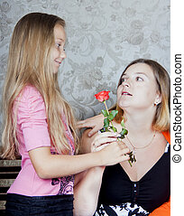 Daughter gives mother a flower