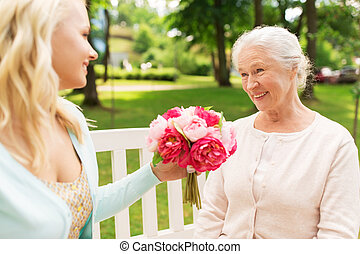 daughter giving flowers to senior mother at park
