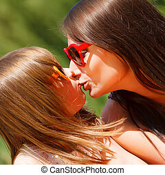 Daughter giving her mother a kiss. Happy family.