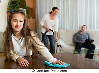 Daughter helping mother to clean, father resting on couch