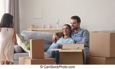 Couple sit on couch near carton boxes while daughter run to parents bring book, kid help parents pack belongings family move to new home prepare renovation flat remodelling, loan or relocation concept