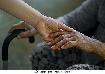 Daughter holding hand of mother elderly that is alzheimer and parkinson patient, Memory loss due to dementia.