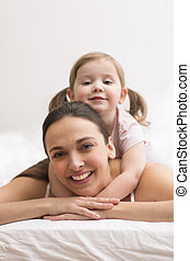 Daughter hugging her mother on the white bed