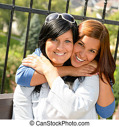 Daughter hugging her mother outdoors happy loving teen...